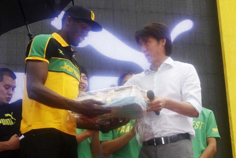 South Korea's Olympic soccer team head coach Hong gives a birthday cake to world and Olympic champion Bolt in Daegu