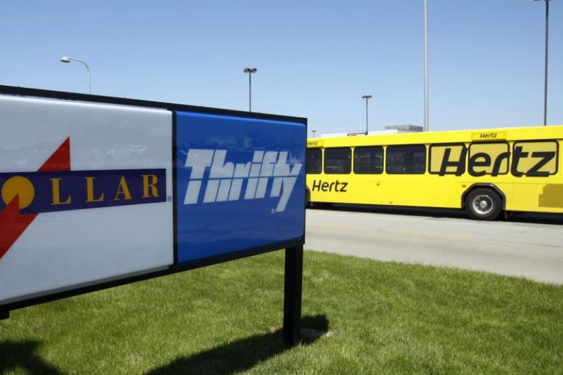 A Hertz rent-a-car shuttle bus drives by a Dollar Thrifty rent-a-car lot in Romulus