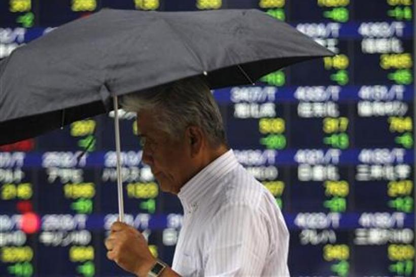 A man walks past an electronic board displaying share prices in Tokyo
