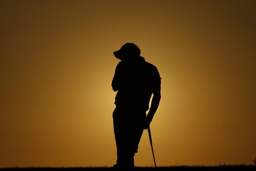 Paul McGinley of Ireland rests on the 18th hole during the first round of the Portugal Master golf tournament
