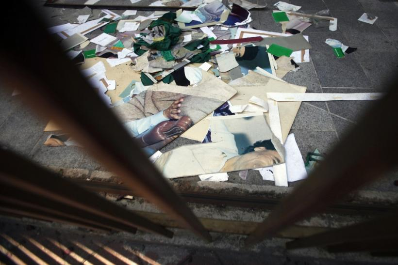 Posters of Gaddafi destroyed by anti-Gaddafi protesters are seen in front of the Libyan embassy in Sarajevo