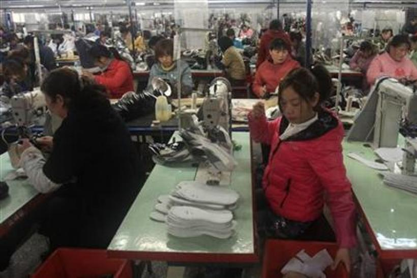 Workers make shoes, which will be exported to the U.S., at a shoe factory in Xihua county