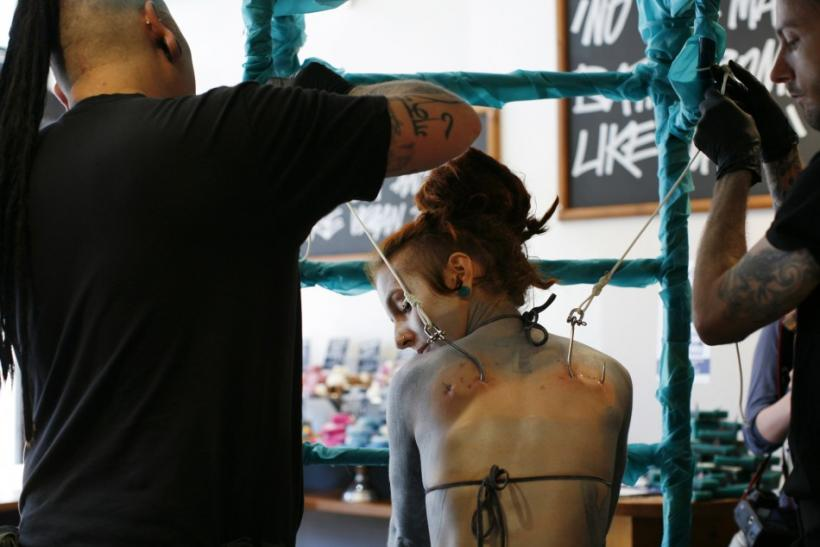 British performance artist Alice Newstead prepares to be suspended from shark hooks at a cosmetic shop in San Francisco