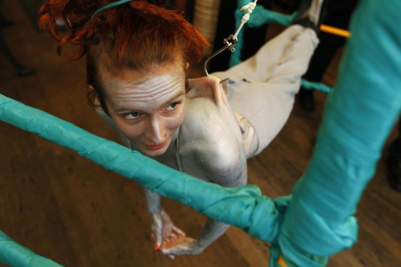 British performance artist Alice Newstead suspends from shark hooks pierced through her back at a cosmetic shop in San Francisco