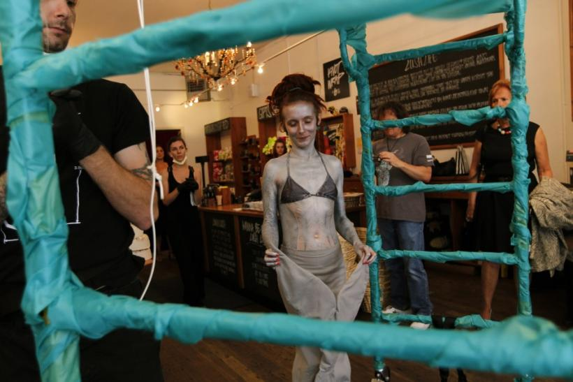 British performance artist Alice Newstead approaches a stand prior to being suspended from shark hooks at a cosmetic shop in San Francisco
