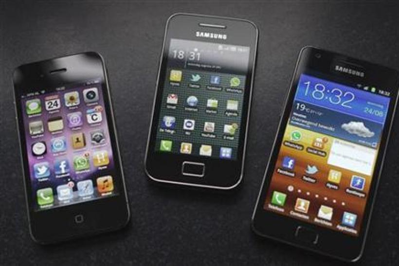 A Samsung S II and Samsung Ace smartphones are seen next to an Apple iPhone 4 in Houten