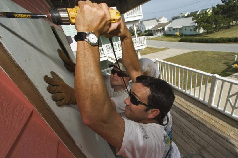 Scott Thomas holds a plywood shutter in position while his brother Brynn Thomas secures it to a window of their beachside home as they prepare for Hurricane Irene in Atlantic Beach