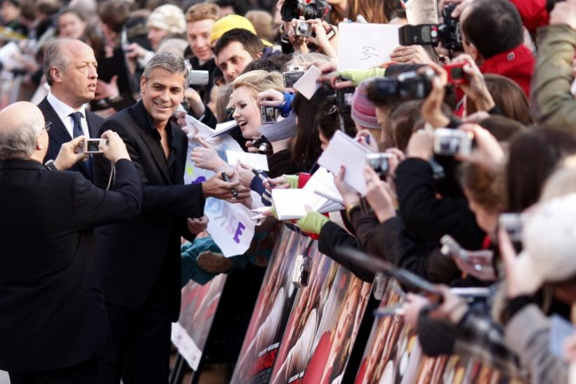"Actor George Clooney signs autographs for fans as he arrives for European premiere of ""Leatherheads"" at Leicester Square Odeon cinema in London"
