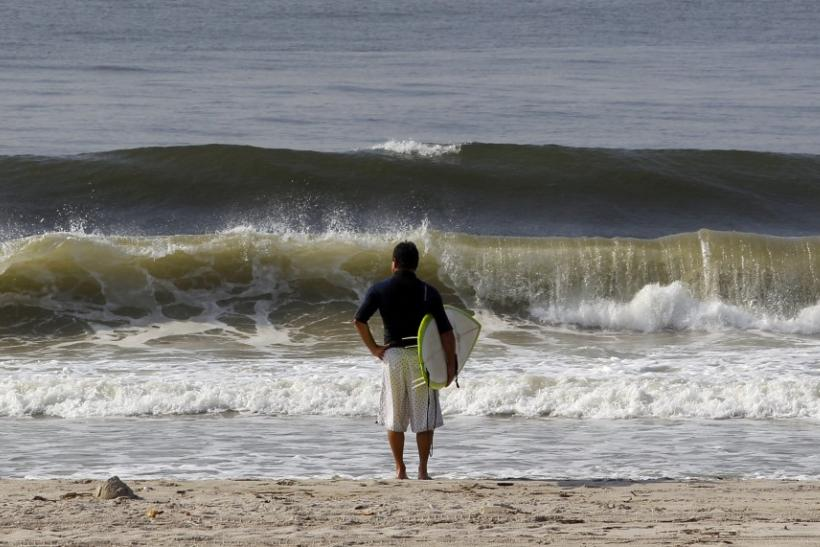 A surfer looks out at the waves on Long Beach on Long Island, New York