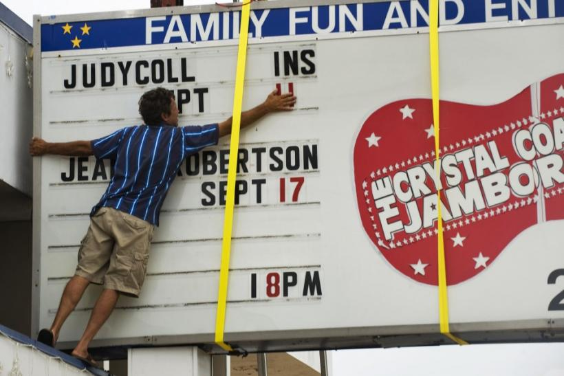 Scott Grafton takes down letters from the marquee of the Morehead Center for Performing Arts as he prepares for the landfall of Hurricane Irene in Morehead City, North Carolina