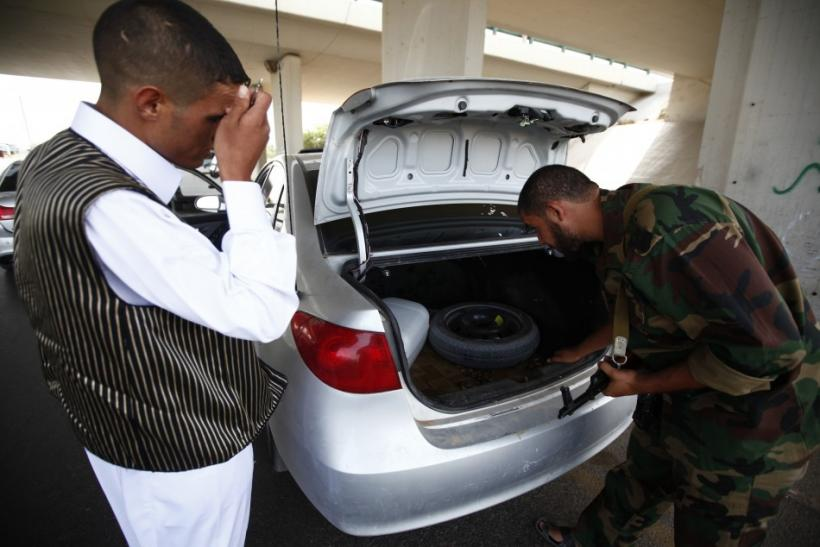 An anti-Gaddafi fighter searches a car at a checkpoint near the airport in Tripoli