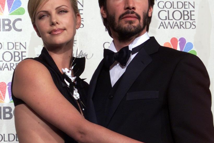 Actress Charlize Theron (L) poses for photos with Keanu Reeves at the 58th annual Golden Globe Awards