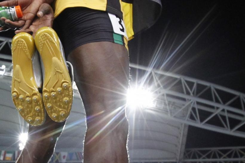 Usain Bolt of Jamaica holds his shoes after winning the men's 200 metres final at the IAAF World Athletics Championships in Daegu