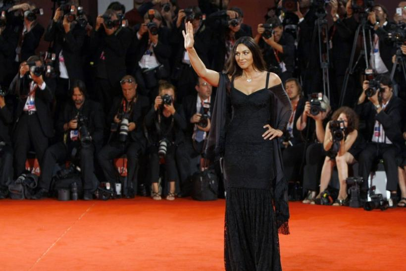"Actress Monica Bellucci poses for photographers as she arrives on the ""Un Ete Brulant"" red carpet at the 68th Venice Film Festival"