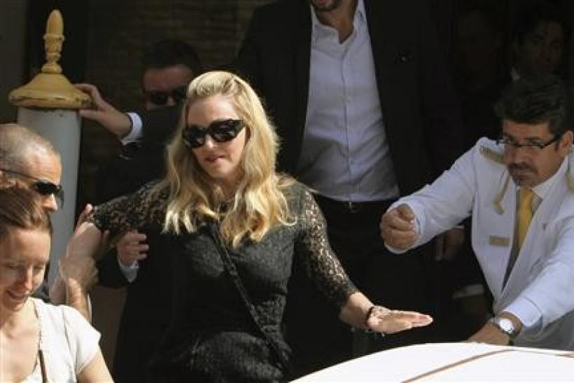 U.S. pop star Madonna, director of movie ''W.E.'', is helped as she leaves by speedboat at her hotel in Venice during the 68th Venice Film Festival