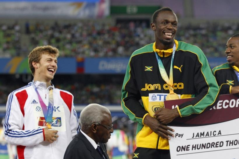 Gold medalists of Jamaica team Usain Bolt (C) and Yohan Blake (R) share a joke with silver medalist Christophe Lemaitre of France (L) during the award ceremony for the men's 4x100 metres relay at the IAAF World Championships in Daegu