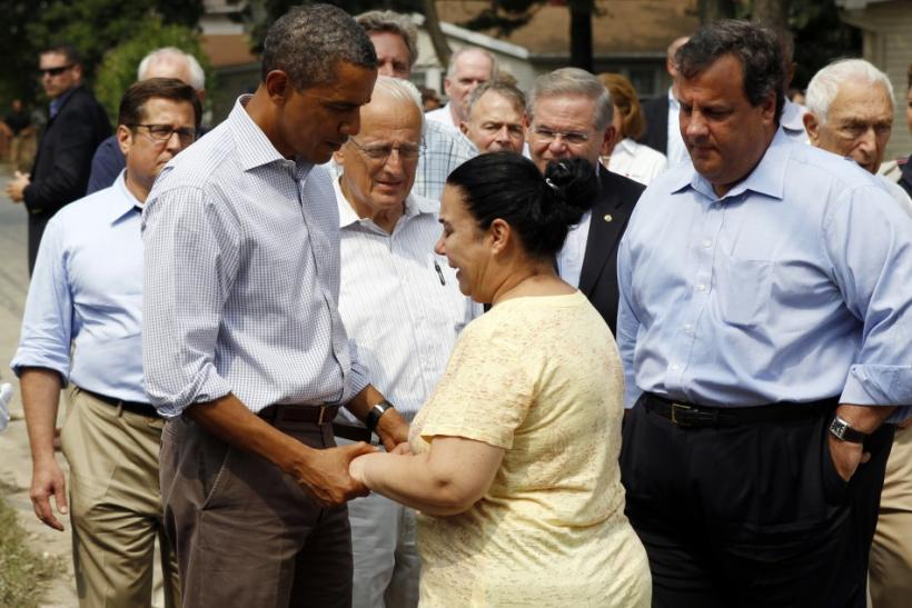 U.S. President Obama holds hands with a woman as he tours damage caused by Hurricane Irene in Wayne, New Jersey