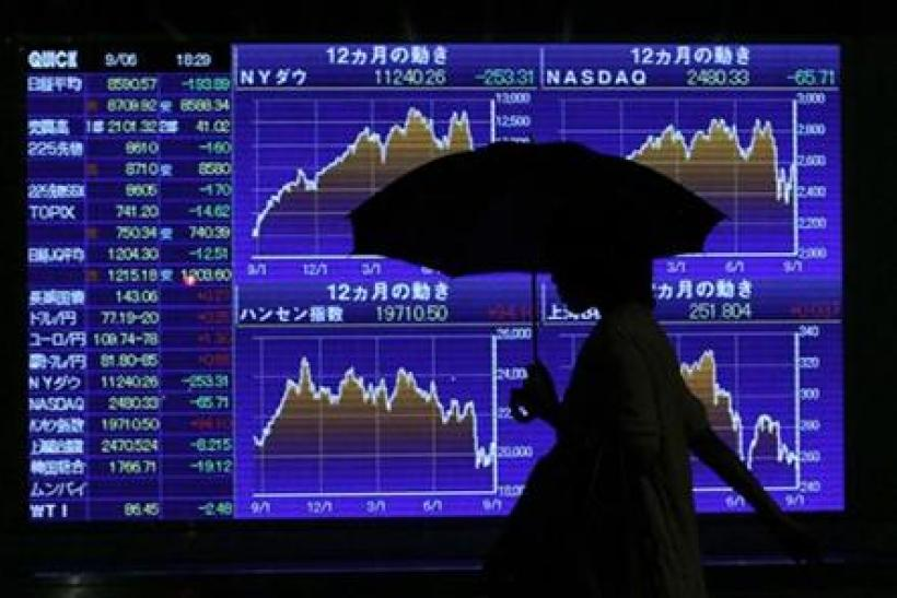 Woman walks past an electronic board displaying market indices outside a brokerage in Toky