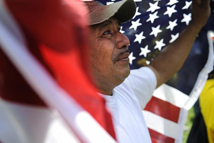 A man weeps and holds a U.S. flag at a May Day rally in Lafayette Square Park near the White House in Washington