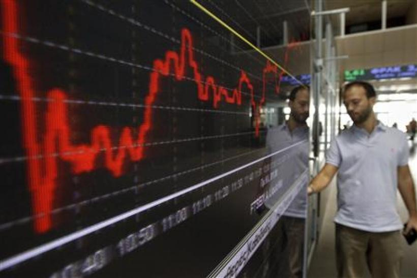 A man stands next to an index board inside the Athens stock exchange