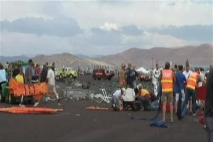 First responders and people help victims in this image taken from a video after a vintage World War Two fighter plane crashed near the grandstand at the Reno Air Races in Reno, Nevada