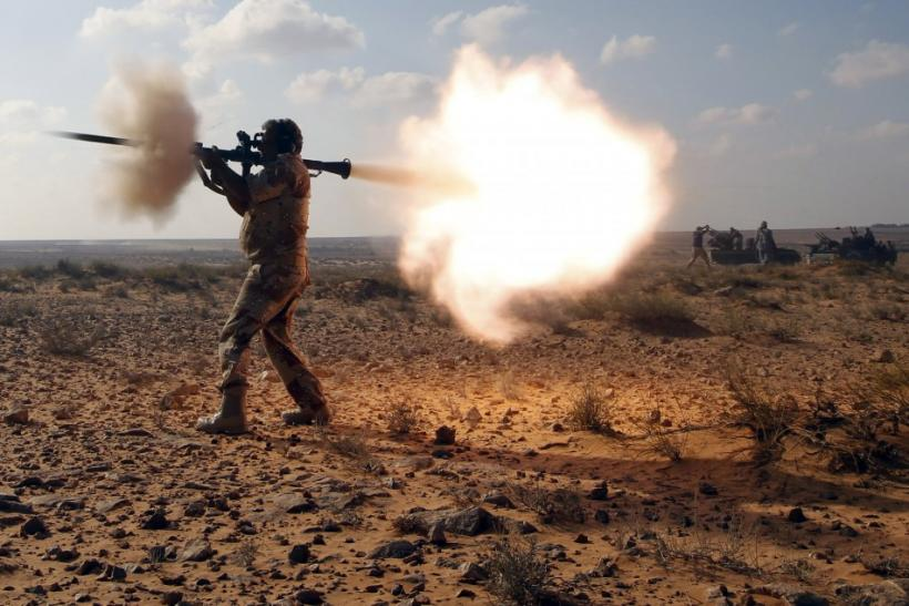 An anti-Gaddafi fighter fires a RPG against Gaddafi loyalists in a village near Sirte