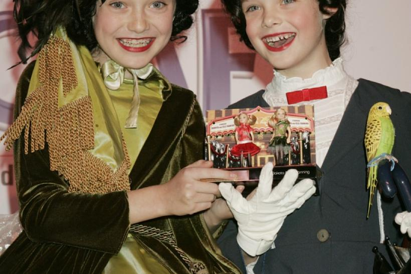 Actresses Dakota (L) and her sister Elle Fanning hold a set one-of-a-kind Polly Pocket dolls.