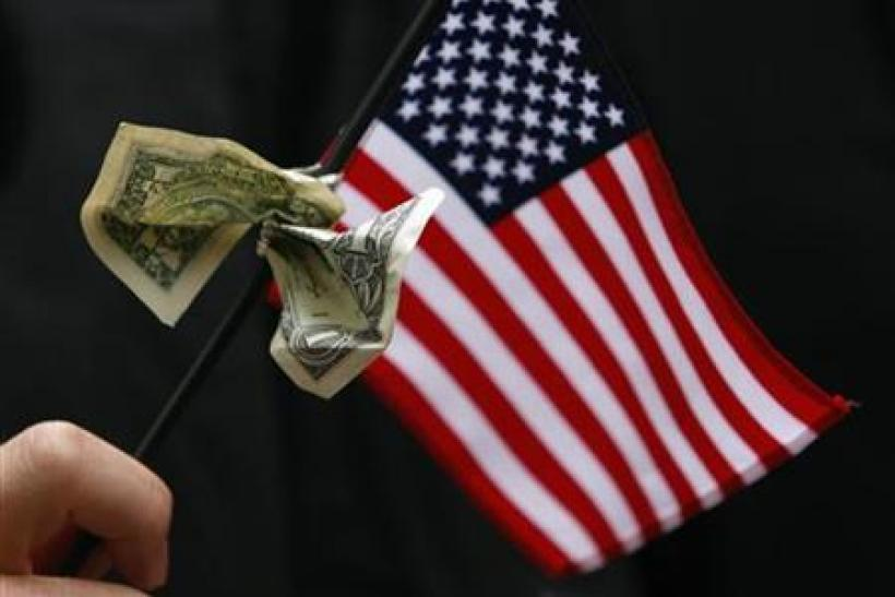 A student graduating from Harvard's Business School holds a U.S. flag with a dollar bill tied to it during the 357th Commencement Exercises at Harvard University in Cambridge