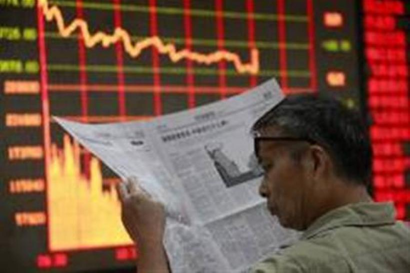 An investor reads a newspaper in front of an electrical board showing stock information at a brokerage house in Huaibei