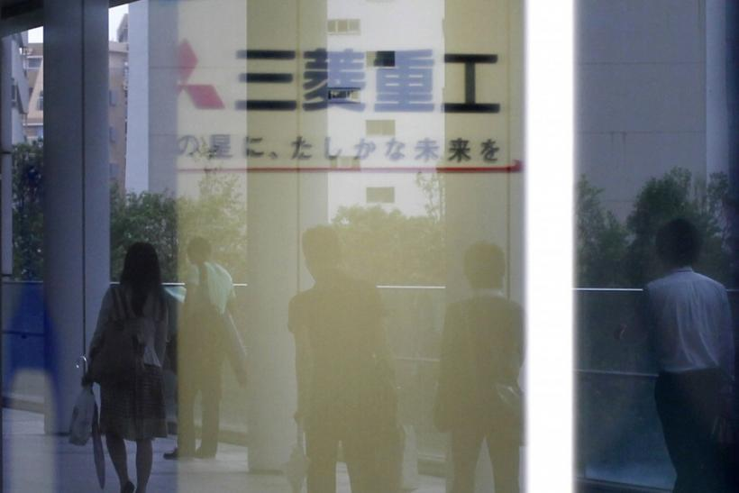 Logo of Mitsubishi Heavy Industries Ltd. is seen as people are reflected on a window at the company headquarters in Tokyo