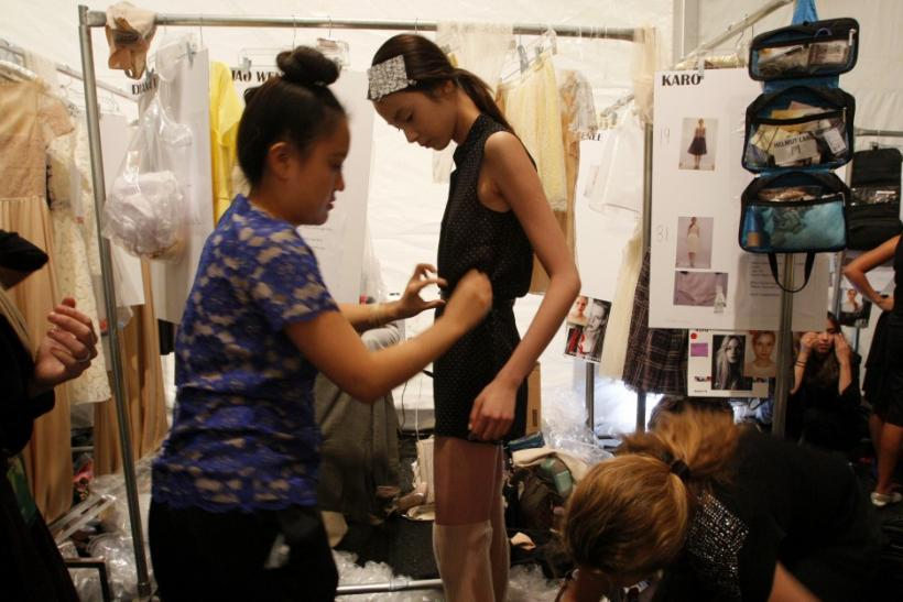 A model gets ready backstage before a showing of the Honor Spring/Summer 2012 collection during New York Fashion Week