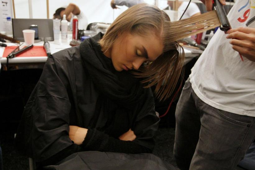 A model sleeps as she gets ready backstage before a showing of the Derek Lam Spring/Summer 2012 collection during New York Fashion Week