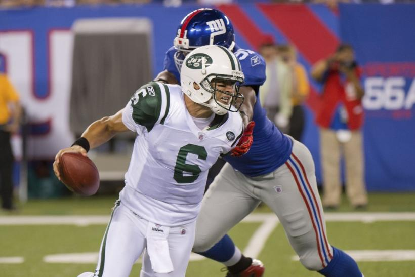 New York Jets Mark Sanchez breaks away from New York Giants Justin Tuck in East Rutherford