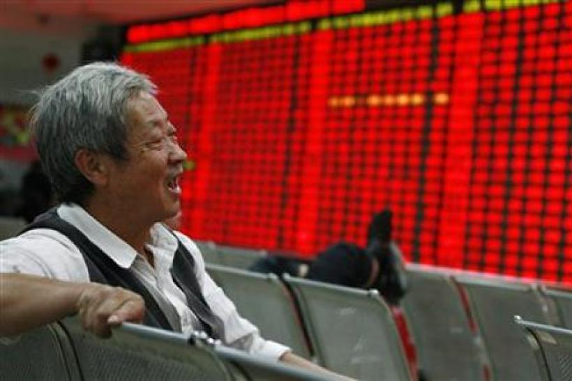 An investor reacts in front of an electronic board showing stock information at a brokerage house in Huaibei