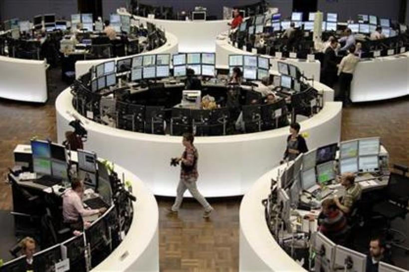 Traders work at their desks in front of the DAX index board at Frankfurt's stock exchange