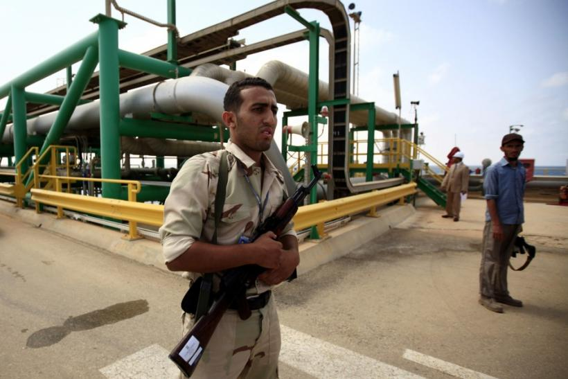 An anti-Gaddafi fighter stands guard at the Mellitah Oil and Gas complex during a handover ceremony in Mellitah