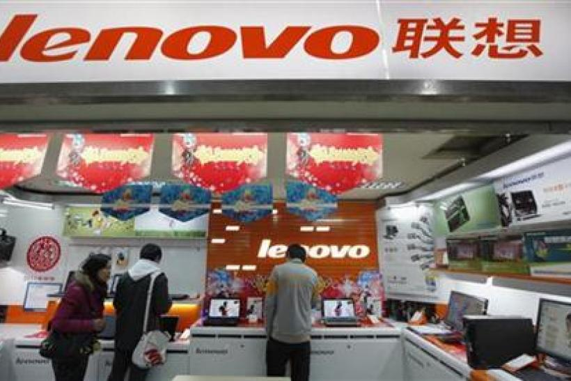 Customers talk to a salesperson about a new laptop at a Lenovo shop in Shanghai