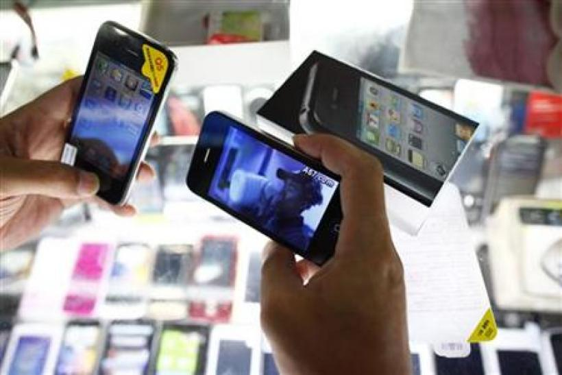 A person holds fake iPhones being sold at a mobile phone stall in Shanghai