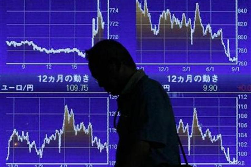 Man looks down as he walks past an electronic board displaying market indices outside a brokerage in Tokyo
