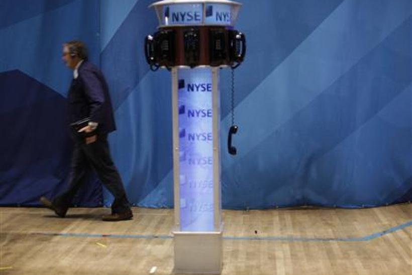A trader walks past a phone hanging off the hook on the floor of the New York Stock Exchange
