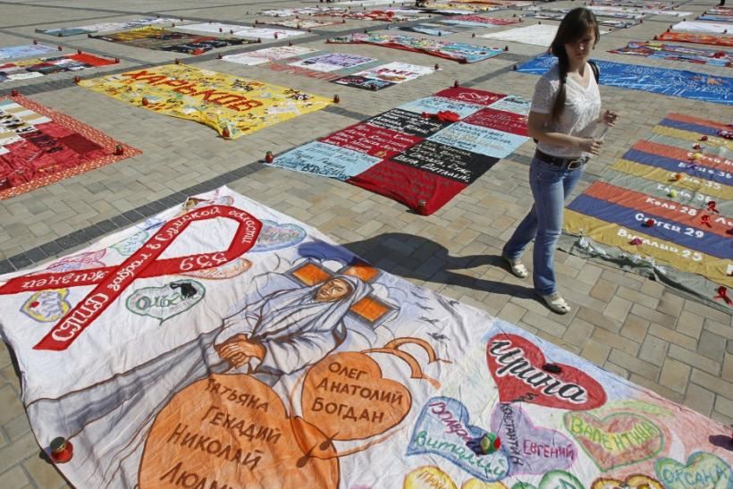 "A woman looks at quilts, created by HIV-positive people, on display during the ""Names"" event in Mikhailovskaya square"