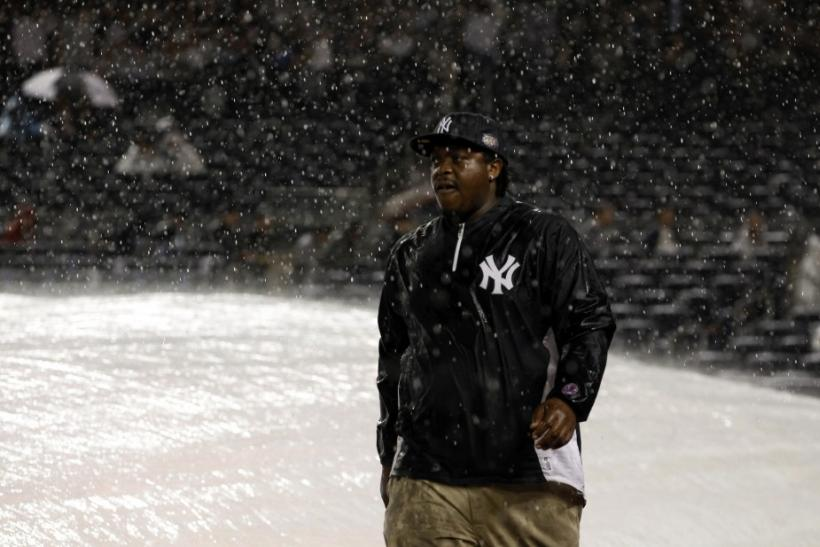 A groundskeeper is pictured during a rain delay in Game 1 of their MLB American League Division Series baseball playoffs between the Yankees and the Tigers in New York