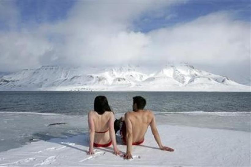 Climate activists Lesley Butler and Rob Bell (R) ''sunbathe'' on the edge of a frozen fjord in the Norwegian Arctic town of Longyearbyen