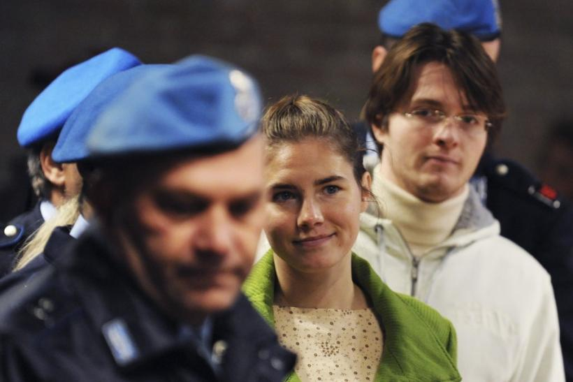 American university student Amanda Knox (C) and her Italian ex-boyfriend Raffaele Sollecito (R) are escorted into courtroom during their murder trial session in Perugia