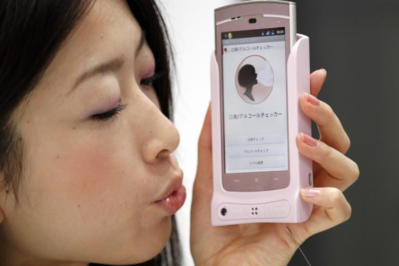 A promotional staff of NTT DoCoMo demonstrates a prototype of smart phone case which measures bad breath at CEATEC JAPAN 2011 electronics show in Chiba, east of Tokyo