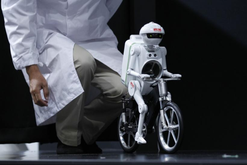 "An employee of Japan's Murata Manufacturing Co. presents the company's bicycle-riding robot ""Murata Seisaku-kun"" at CEATEC JAPAN 2011 electronics show in Chiba, east of Tokyo"