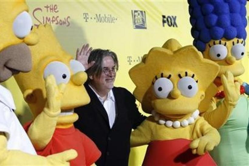 Matt Groening (C), creator of The Simpsons, poses with characters from the show (L-R) Homer, Bart, Lisa and Marge at the 20th anniversary party for the television series at Barker hangar in Santa Monica, California