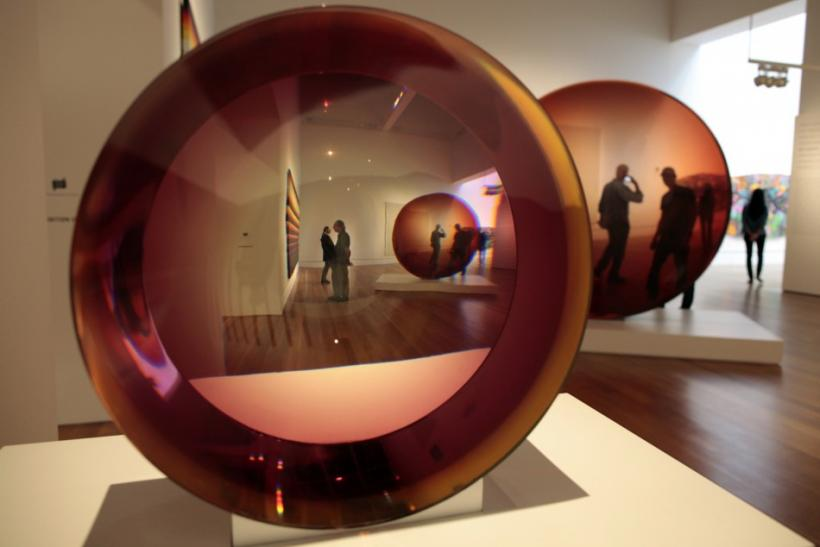 """In an optical illusion Red Concave Circle by De Wain Valentine (R) is seen twice through """"Untitled"""" by Frederick Eversley at the """"Pacific Standard Time: Art in L.A. 1945-1980"""" exhibition at the Getty Center in Los Angeles, California"""