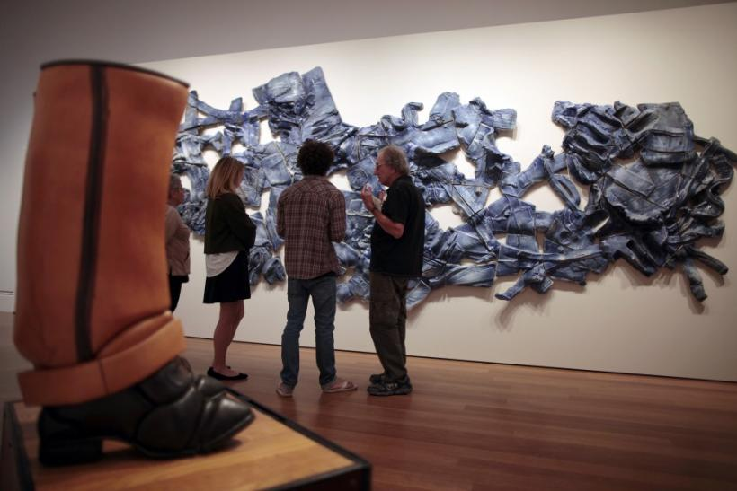 """People view """"Tap Dancer"""" by Stephan von Huene (L) and """"Blue Wall"""" by John Mason at the """"Pacific Standard Time: Art in L.A. 1945-1980"""" exhibition at the Getty Center in Los Angeles, California"""