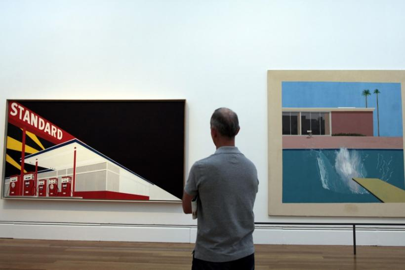 """A man views """"Standard Station"""" by Ed Ruscha and """"A Bigger Splash"""" by David Hockney at the """"Pacific Standard Time: Art in L.A. 1945-1980"""" exhibition at the Getty Center in Los Angeles, California"""